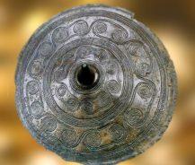 D'après un disque de ceinture, bronze, à enchaînement de spirales, Danemark,âge du Bronze. (Marsailly/Blogostelle)