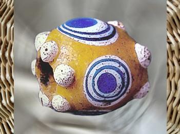 D'après une perle en pâte de verre colorée, à motifs circulaires et boules en haut relief, Picardie, La Tène, Gaule celtique, âge du Fer. (Marsailly/Blogostelle)