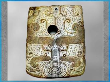 """D'après un objet de prestige, jade, motif face de """"glouton"""", en forme de hache symbole de pouvoir, vers 4300-2600, période Beixin-Dawenkou, néolithique, Chine ancienne. (Marsailly/Blogostelle)"""