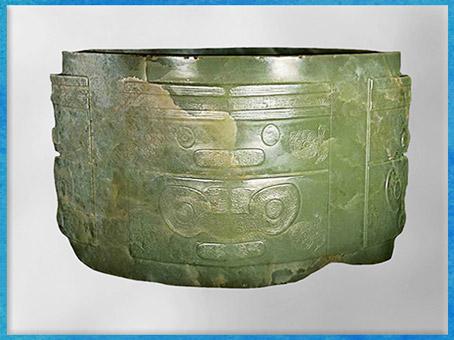 D'après un cylindre sculpté, jade vert, motif mufle-taotie, culture de Liangzhu, 3200-2200 avjc, fin néolithique, Chine ancienne. (Marsailly/Blogostelle)